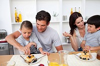 Young family having breakfast together in the kitchen