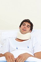 Young patient with a neck brace lying on a hospital bed