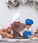 Father baking cookies with his children in the kitchen