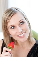 Portrait of a bright woman eating a strawberry