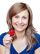Beautiful woman eating strawberries against a white background