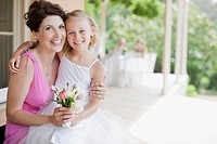 Woman hugging flower girl (thumbnail)