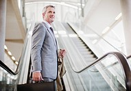 Businessman standing near escalator (thumbnail)