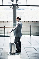 Businessman waiting with suitcase in train station