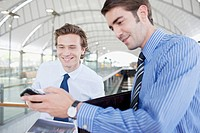 Businessman showing co_worker text message