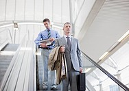 Businessmen descending escalator