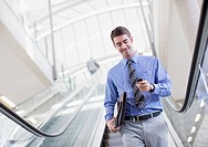 Businessman with mp3 player descending escalator