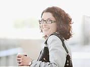 Smiling businesswoman holding coffee