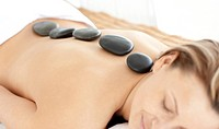 Relaxed woman with hot stones on her back in a Spa center