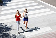 Friends running across urban crosswalk