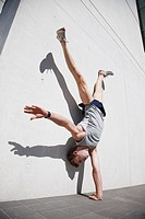 Man doing handstand in urban setting