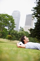 Man laying in urban park with soccer ball