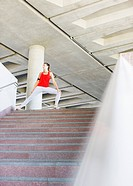 Woman stretching on staircase before exercise