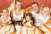Familie mit Katze im Bett beim Frühstück