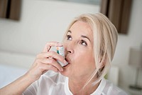 Close_up of a woman using an asthma inhaler