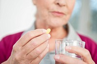 Close_up of a woman taking a capsule