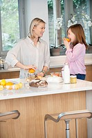 Woman making orange juice with her daughter in the kitchen