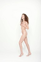 Naked woman covering her breasts