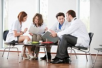 Doctors sitting on chairs discussing medical reports