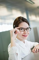 Portrait of a businesswoman adjusting her eyeglasses and smiling