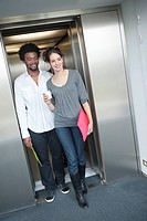 Businesswoman coming out from an elevator with her colleague (thumbnail)