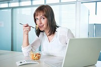 Businesswoman eating pasta in front of a laptop