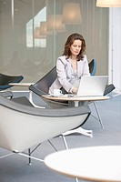 Businesswoman sitting on a chair and using a laptop
