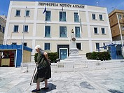 Old woman walking front Syros Town Hall, Cyclades Islands, Greece