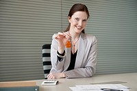 Female real estate agent holding house keys in an office (thumbnail)