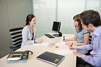 Couple signing agreement form in a real estate agent´s office
