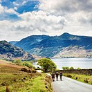 Walkers on the road past Crummock Water the Lake District Cumbria England UK with High Stile and Red Pike