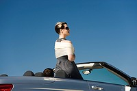 Young woman standing up in convertible looking at view