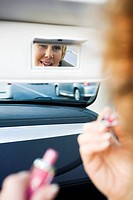Woman in car putting on makeup using visor vanity mirror