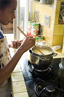 Girl stirring pot on stove