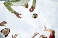 Father and sons playing with soccer ball, low angle view (thumbnail)