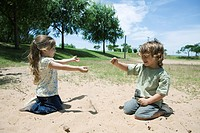 Young children playing in sand at park