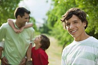 Teenage boy outdoors with father and younger brothers, portrait
