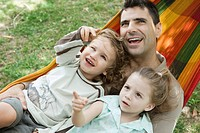 Father and two children relaxing together in hammock