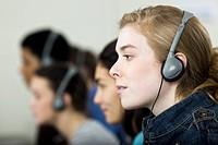 High school students listening to headphones, profile