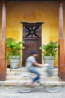 Man cycling past doorway in Old Town of Galle Fort, Galle, Sri Lanka