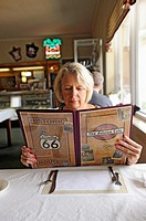 Woman looks at menu in Historic Ariston Cafe along Route 66 Litchfield Illinois