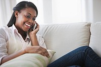 African American woman using cell phone on sofa