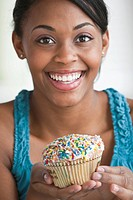 African American woman holding cupcake