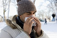 Mixed race man blowing nose outdoors