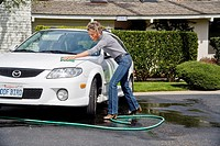 Using a bucket of detergent and a garden hose, an adult woman washes her car with a sponge outdoors in Laguna Niguel, California
