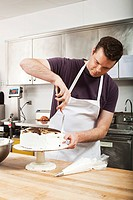 Male chef icing a cake in commercial kitchen