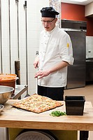 Male chef making pizza in commercial kitchen