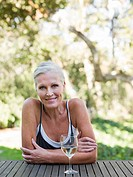 Mature woman outdoors with wine