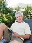 Senior man on sun lounger with book (thumbnail)