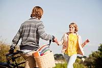 Young woman running to boyfriend on bike